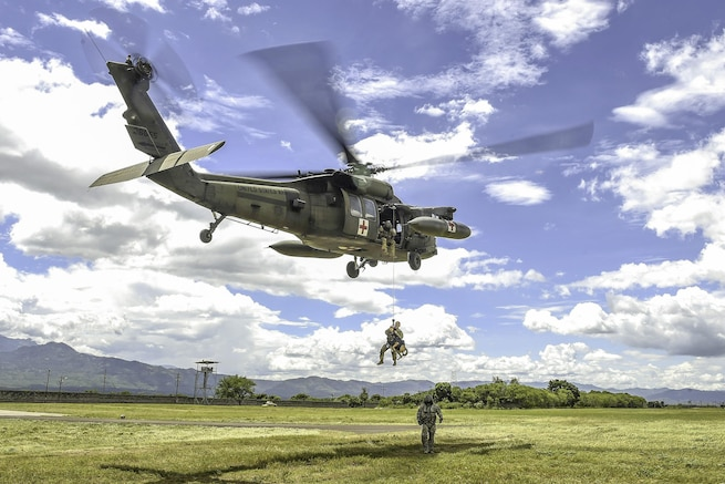 A UH-60L Black Hawk helicopter hoists Army Spc. Courtney Moreland, a military working dog handler, and her dog, Puma, during K-9 evacuation training at Soto Cano Air Base, Honduras, Aug. 15, 2016. Moreland is assigned to Joint Task Force Bravo's Joint Security Forces. Air Force photo by Staff Sgt. Siuta B. Ika