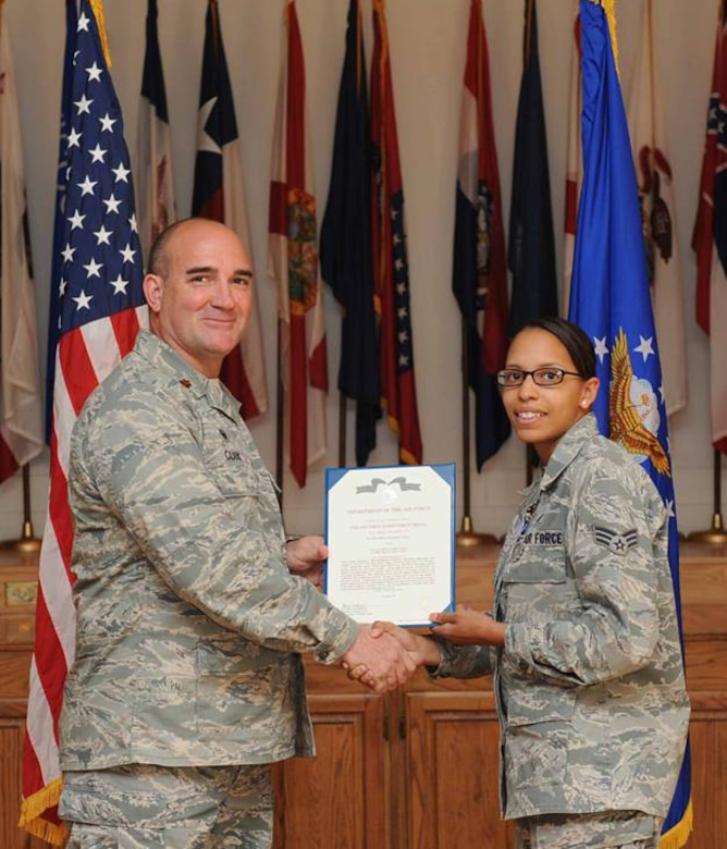 U.S. Air Force Maj. Brant Clark, 7th Comptroller Squadron commander, awards Senior Airman Shannon Hall, 7th Bomb Wing Public Affairs photojournalist the Air Force Achievement Medal April 23, 2014, at Dyess Air Force Base, Texas.  Hall received the medal after completing numerous hours of funerals, retirements and other ceremonies while a member of the Dyess Honor Guard. (U.S. Air Force photo by Airman 1st Class Alexander Guerrero/Released)