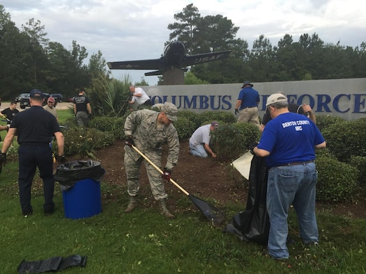 More than 20 Columbus community members and base personnel work together to clean up the landscape around the T-37 static Display on Highway 45 Aug. 20 in front of Columbus Air Force Base, Mississippi. (Courtesy Photo)