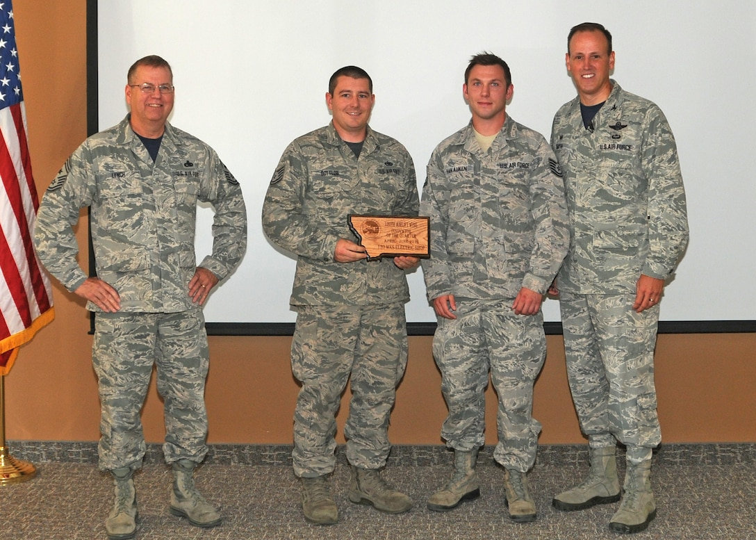 120th Airlift Wing Commander Col. Lee Smith and 120th AW Command Chief, Chief Master Sgt. Steven Lynch, present the Innovator of the Quarter Award to Tech. Sgts. Keith Gottlob and Ronald Van Auken during a commander's call held in the Larsen Room of the Wing Headquarters Building during the regularly scheduled drill August 13, 2016. (U.S. Air National Guard photo by Staff Sgt. Lindsey Soulsby)