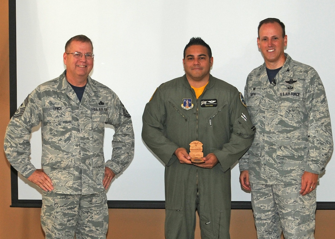 120th Airlift Wing Commander Col. Lee Smith and 120th AW Command Chief, Chief Master Sgt. Steven Lynch, present the Field Grade Officer of the Quarter Award to Maj. Tirso Pena during a commander's call held in the Larsen Room of the Wing Headquarters Building during the regularly scheduled drill August 13, 2016. (U.S. Air National Guard photo by Staff Sgt. Lindsey Soulsby)
