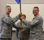 Lt. Col. David Bartczak, right, takes the guidon from 224th Air Defense Group Commander Col. John Balbierer during the Aug. 18 Support Squadron assumption of command ceremony at the Eastern Air Defense Sector. Chief Master Sgt. Maureen Dooley, the Senior Enlisted Advisor at the 224th ADG, is in the back.