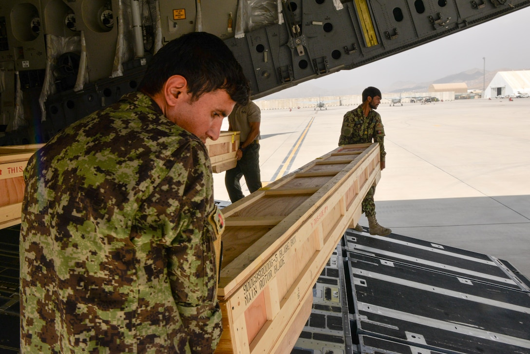 Members from the Afghan air force unload crates containing rotar blades at Hamid Karzai International Airport, Kabul, Afghanistan, Aug. 25, 2016. The blades were delivered on a C-17 Globemaster III from Travis Air Force Base, Calif., along with the final four MD-530 Cayuse Warrior helicopters the AAF will receive, bringing the total number to 27. (U.S. Air Force photo by Tech. Sgt. Christopher Holmes)