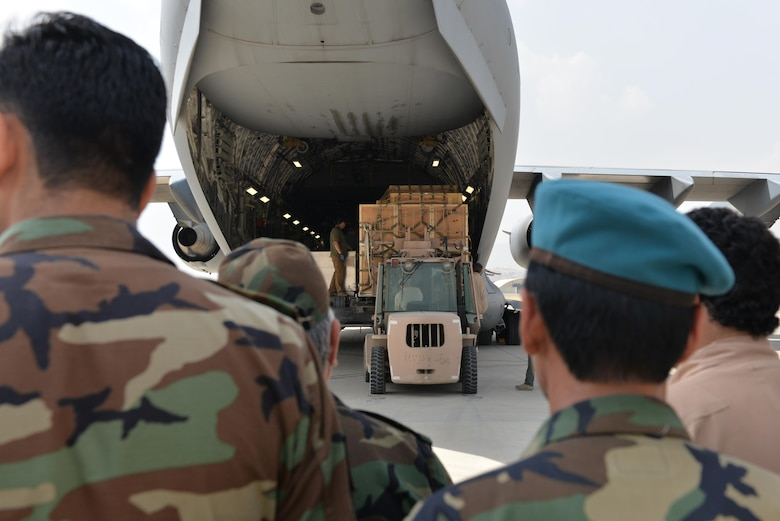 Members of the Afghan air force watch as crates are unloaded from a C-17 Globemaster III from Travis Air Force Base, Calif., at Hamid Karzai International Air Port, Kabul, Afghanistan, Aug. 25, 2016. The crates contained ramps that were used to unload four MD-530 Cayuse Warrior helicopters. The helicopters are the last ones to be delivered to the AAF, bringing their total number to 27. (U.S. Air Force photo by Tech. Sgt. Christopher Holmes)