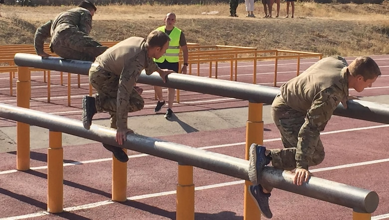 Team USA 3 tackles the second obstacle on the 500 meter, NATO-standard, obstacle course.  Each member must touch one foot between the two bars and then vault the higher bar.  (L to R)1st Lt. Sterling Broadhead, Capt. Chuck Francis and 2nd Lt. Nate Davis (Mississippi Army National Guard).