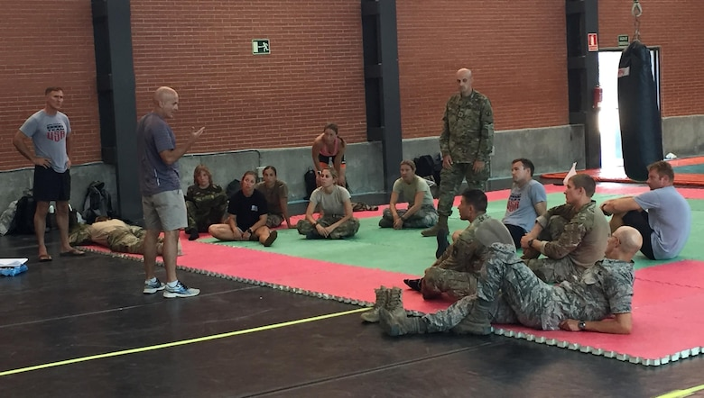 After an exhausting day on the land obstacle course, Lt. Col. Daryl Remick (center, standing) former competitor, Georgia Army National Guard and full-time emergency room physician, teaches Tactical Combat Casualty Care, ably assisted by Staff Sgt. Reuben Sublett (standing right), Army Reserve Medic.