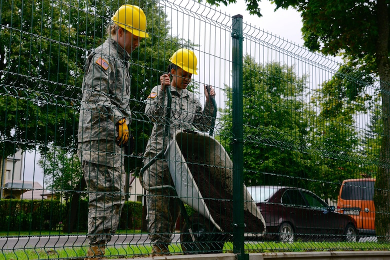U.S. Army Spc. Ashley Clark (left) and Spc. Raven Henderson (right), both assigned to the 375th Engineer Company, 467th Engineer Battalion, 926th Engineer Brigade, 412th Theater Engineer Command, assist with constructing a fence during a Humanitarian Civil Assistance (HCA) project, in Sauliai, Lithuania, Aug. 18, 2016. As part of the European Command's (EUCOM) Humanitarian and Civic Assistance Program, the 375th Engineer Company, 457th Civil Affairs Battalion and the Lithuanian military collaborate to renovate the fence at Kudikiu Namai, an orphanage for Lithuanian children up to the age of 6, in Sauliai, Lithuania, August 8-26, 2016. The Humanitarian and Civic Assistance Program is a series of medical and engineering engagements in several European countries in support of strategic, theater, operational and tactical objectives. (U.S. Army photo by Pfc. Emily Houdershieldt)