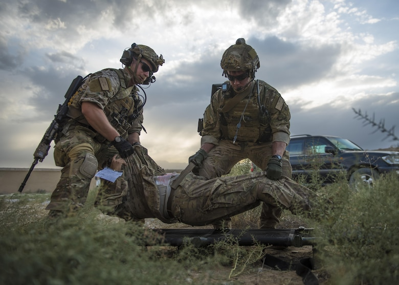 Senior Airmen Kyle Green, left, and Ty Hatcher, both 83rd Expeditionary Rescue Squadron pararescue specialists, lift a patient onto a litter during a mass casualty and extraction exercise at Bagram Airfield, Afghanistan, Aug. 18, 2016. Airmen from various units acted as patients with injuries that included broken limbs, deliria and head wounds. (U.S. Air Force photo/Senior Airman Justyn M. Freeman)