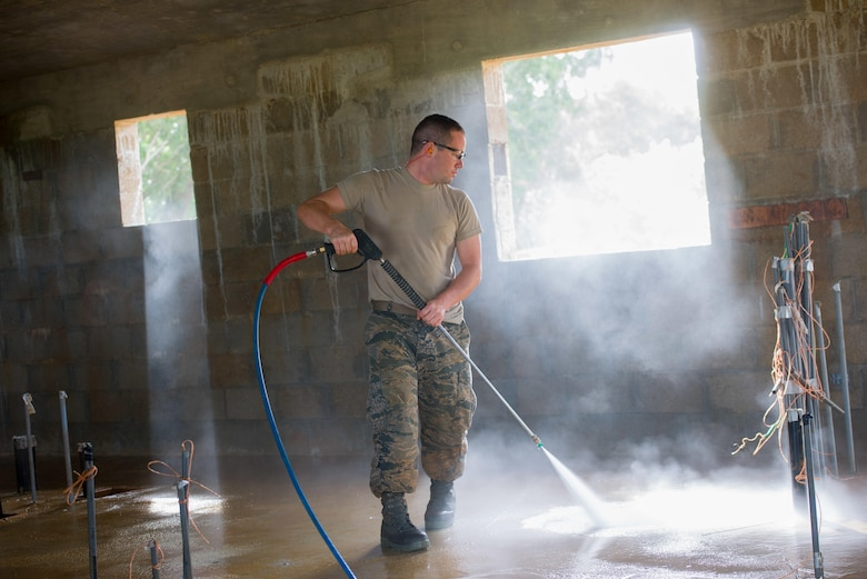 Tech. Sgt. Justin Gooden, a 134th Air Refueling Wing engineering apprentice, power washes the interior of a home in Malojloj, Guam, in preparation of interior construction. Airmen of the 134th ARW work on two Habitat for Humanity homes in Guam as part of a government initiative that allows military assets the opportunity to assist non-profit organizations in conjunction with scheduled annual training. (U.S. Air National Guard photo/Tech. Sgt. Jonathan Young)