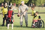 Marine Corps Sgt. Maj. Craig D. Cressman plays flag football with children during an NFL Play 60 event at Fort Belvoir, Va., Sept. 30, 2014. Army photo by Rachel Larue