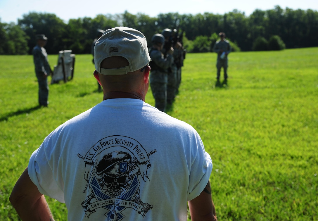 Tommy Hutfles, a 509th Security Forces Squadron instructor, watches as Airmen from the 509th Munitions Squadron (MUNS) participate in shoot, move and communicate training at Whiteman Air Force Base, Mo., Aug. 18, 2016. During the training, members of the 509th MUNS would pair up in teams of two, while providing cover fire and advance or fall back from their positions while firing their weapon at a target, suppressing a simulated enemy. (U.S. Air Force photo by Senior Airman Joel Pfiester)