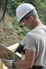 Staff Sgt. Dominick Tami, a Civil Engineer structural engineer, uses a nail gun to secure a piece of treated lumber to the new staircase leading from the Veteran's Park to the riverside here, Aug. 25, 2016. Tami is a member of a small team from the 910th Civil Engineer Squadron, based at nearby Youngstown Air Reserve Station (YARS), Ohio, who teamed up with the City of Newton Falls to undertake a three-week project to demolish the existing staircase and design and build the new stairs under Department of Defense's Realistic Military Training program and the Air Force Community Partnership Program. The program is designed to identify and develop mutually beneficial partnerships between Air Force installations and surrounding communities. (U.S. Air Force photo/Master Sgt. Bob Barko Jr.)