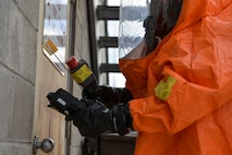 U.S. Army Staff Sgt. Andrew Markham, an Alaska Army National Guard Chemical, Biological, Radiological and Nuclear noncommissioned officer assigned to the 103rd Weapons of Mass Destruction-Civil Support Team out of Kulis Air National Guard Base, Alaska, checks a door for harmful substances during an exercise Aug. 23, 2016, at the Fairbanks Regional Fire Training Center in Fairbanks, Alaska. Air monitors with different sensors are used to check for various substances in the air. (U.S. photo by Air Force Airman Isaac Johnson)