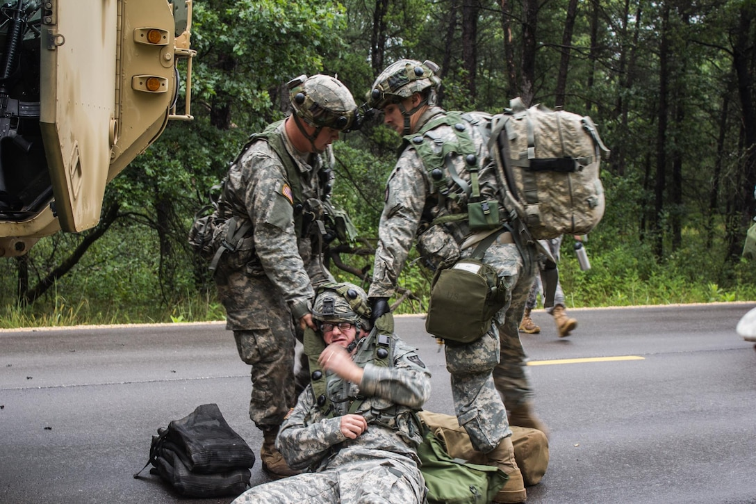 FORT MCCOY, Wis. – U.S. Army Reserve Soldiers, with the 397th Engineering Battalion from Eau Claire, Wis., pull a victim of a mock roadside attack to safety. U.S. Army Reserve medic, Pfc. Gage Theisen (right) administers first-aid and prepares victims for medical evacuation during a combat support training exercise Aug. 20, 2016 at Fort McCoy, Wis. (U.S. Army Reserve photo by Sgt. Clinton Massey, 206th Broadcast Operations Detachment)