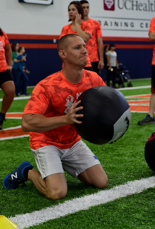 Staff Sgt. Matthew Campbell, 460th Medical Support Squadron logistics NCO in charge, throws a medicine ball during a kneeling power ball launch of a military training camp at the Denver Broncos' University of Colorado Health Training Center Fieldhouse in Englewood, Colo., August 25, 2016. Team Buckley won the military camp competition after participating in five head-to-head challenges including: team ball catching, a gauntlet, tackling dummy relay, sled push and the kneeling power ball launch. (U.S. Air Force photo by Airman 1st Class Gabrielle Spradling/Released)