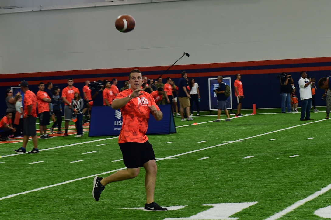 2nd Lt. Colin Wolff, 460th Space Wing space operations officer, catches a football during the team ball catching portion of a military training camp at the Denver Broncos' University of Colorado Health Training Center Fieldhouse in Englewood, Colo., August 25, 2016.  Team Buckley won the military camp competition after participating in five head-to-head challenges including: team ball catching, a gauntlet, tackling dummy relay, sled push and the kneeling power ball launch. (U.S. Air Force photo by Airman 1st Class Gabrielle Spradling/Released)
