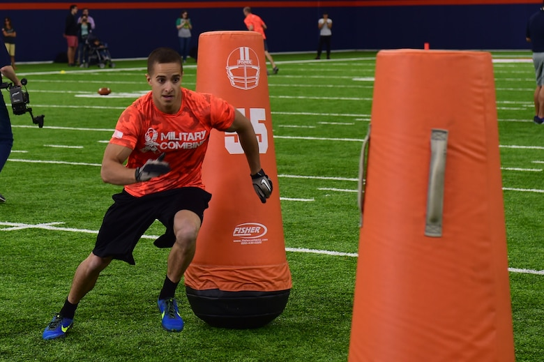 1st Lt. James Macandrew, 460th Space Wing Commanders Action Group chief, runs through tackling dummies during the five-man obstacle course of a military training camp at the Denver Broncos' University of Colorado Health Training Center Fieldhouse in Englewood, Colo., August 25, 2016. Team Buckley won the military camp competition after participating in five head-to-head challenges including: team ball catching, a gauntlet, tackling dummy relay, sled push and the kneeling power ball launch. (U.S. Air Force photo by Airman 1st Class Gabrielle Spradling/Released)