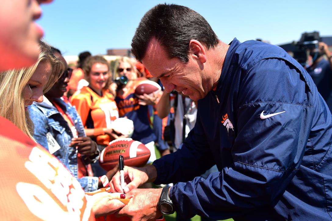Gary Kubiak, Denver Broncos' head coach, signs autographs during a military training camp at the Denver Broncos' University of Colorado Health Training Center Fieldhouse in Englewood, Colo., August 25, 2016. The camp invited ten, five member teams to compete against each other and be a part of the NFL boot camp experience. (U.S. Air Force photo by Airman 1st Class Gabrielle Spradling/Released)