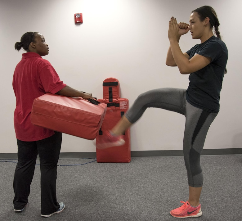 Senior Airman Emily Pearce, 11th Security Forces Squadron response force leader, delivers a kick to a bag held by Staff Sgt. Shandralekha Carlos, 11th Wing Commander's Action Group NCO in charge, during a Rape Aggression Defense class at Joint Base Andrews, Md., Aug. 20, 2016. The R.A.D. class is a self-defense program teaching basic self-defense tactice and avoidance techniques for risk factors. (U.S. Air Force photo by Airman 1st Class Rustie Kramer)