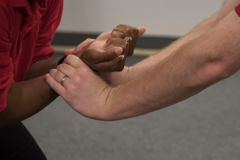Staff Sgt. Shandralekha Carlos, 11th Wing Commander's Action Group NCO in charge, and Staff Sgt. Kevin Maeder, 11th Security Support Squadron security forces instructor, demonstrate how to break a wrist grab during a Rape Aggression Defense class at Joint Base Andrews, Md., Aug. 20, 2016. The R.A.D. class is a self-defense program teaching basic self-defense tactics and avoidance techniques for risk factors. (U.S. Air Force photo by Airman 1st Class Rustie Kramer)