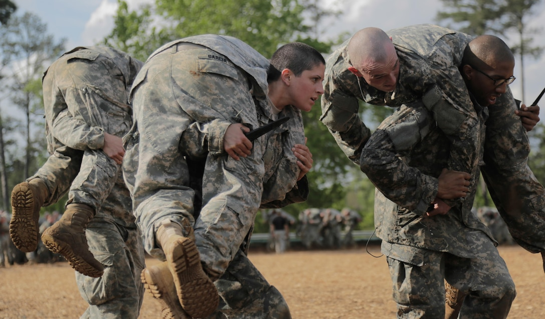U.S. Army Capt. Kristen Griest, middle, carries a fellow Soldier as part of combative training during the Ranger Course on Ft. Benning, GA., April 20, 2015. 19 female soldiers, including Griest, made history when they began the first gender-integrated Ranger Course assessment. Soldiers attend Ranger school to learn additional leadership and small unit technical and tactical skills in a physically and mentally demanding, combat simulated environment. (U.S. Army photo by Spc. Nikayla Shodeen/Released)