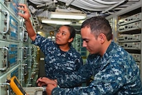 Navy Petty Officer 2nd Class Laura A. Hale and Petty Officer 3rd Class Martin Rodriguez do troubleshooting work in the radio room aboard the USS Bataan in Norfolk, Va., Aug. 18, 2016. Hale is an information systems technician; Rodriguez is an electronics technician. Navy photo by Seaman Apprentice Zachariah Grabill