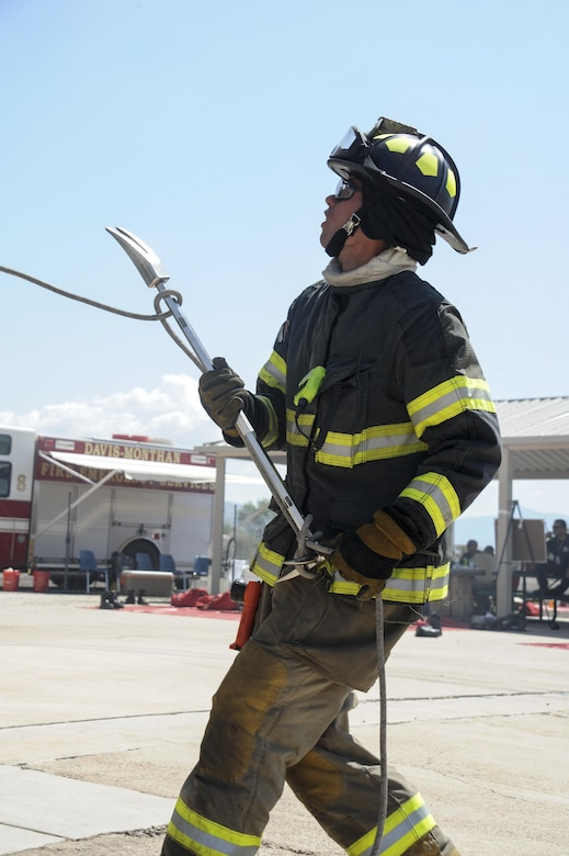 A firefighter from the Green Valley Fire District hoists a Halligan bar during live-fire training at Davis-Monthan Air Force Base, Ariz., Aug. 24, 2016. Members of the 355th Civil Engineer Squadron's Fire and Emergency Services and the Green Valley Fire District participated in live-fire Class A training over the course of four days on D-M AFB's fire training grounds. (U.S. Air Force photo by Airman 1st Class Mya M. Crosby)
