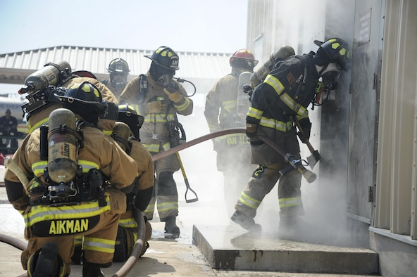 U.S. Airmen assigned to the 355th Civil Engineer Squadron and firefighters from Green Valley Fire District prepare to enter into a burn house at Davis-Monthan Air Force Base, Ariz., Aug. 24, 2016. Members of the 355th CES's Fire and Emergency Services and the Green Valley Fire District participated in live-fire Class A training over the course of four days on D-M AFB's fire training grounds. (U.S. Air Force photo by Airman 1st Class Mya M. Crosby)