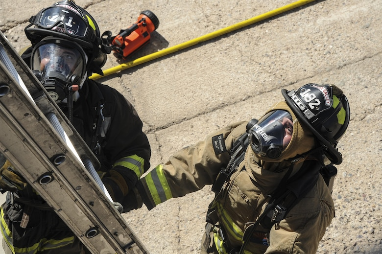 Firefighters from the Green Valley Fire District position a ladder during live-fire training at Davis-Monthan Air Force Base, Ariz,. Aug. 24, 2016. Members of the 355th Civil Engineer Squadron's Fire and Emergency Services and the Green Valley Fire District participated in live-fire Class A training over the course of four days on D-M AFB's fire training grounds. (U.S. Air Force photo by Airman 1st Class Mya M. Crosby)