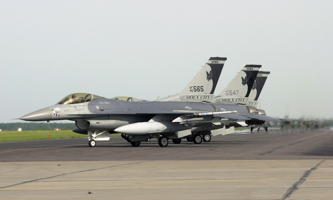 "Three U.S. Air Force F-16's assigned to the 185th Fighter Wing, Sioux City, Iowa on the ramp at Cold Lake, Alberta, CA. participate in the multinational air exercise ""Maple Flag"" on June 12, 2001. The Iconic Gothic Bat tail flash, created by 185th graphic artist Technical Sgt. Frank Rosales, proudly displays the unit's nickname ""Bats"" that was earned when the unit was in Vietnam.
