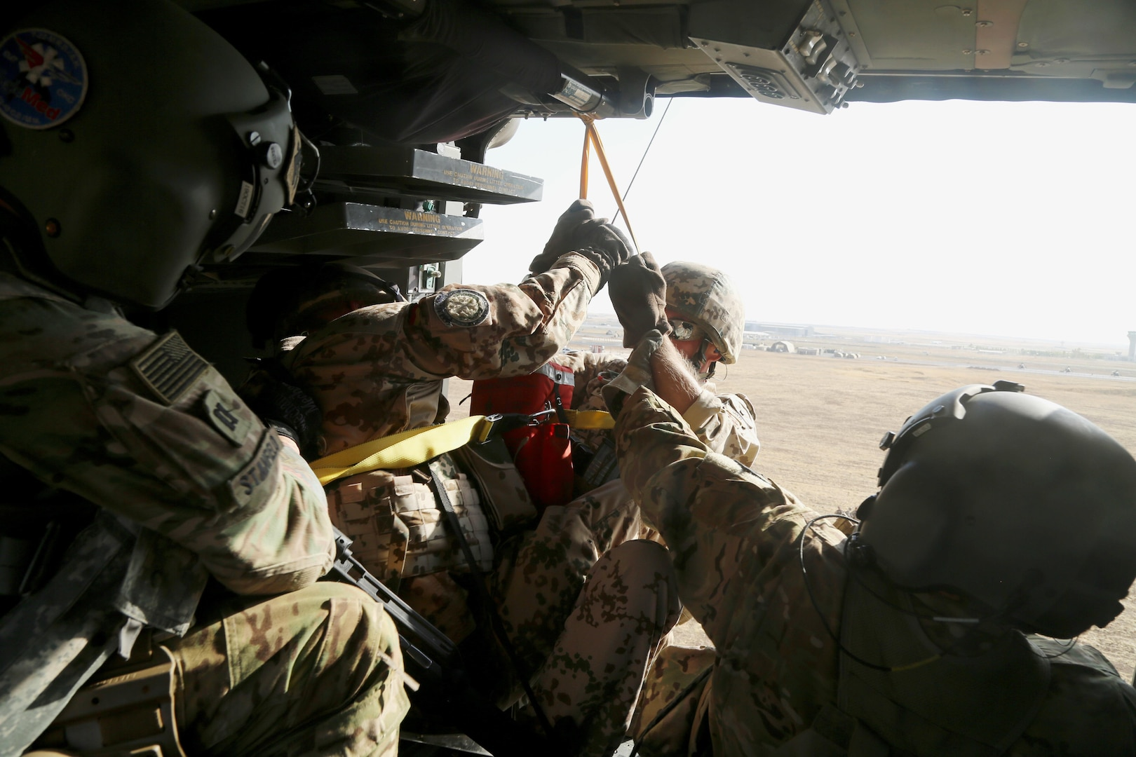 U.S. Army Capt. Ryan Stanfield, a flight nurse, and Sgt. Jared Belisle, a crew chief, both assigned to Company C, 1st General Support Aviation Battalion, 111th Aviation Regiment, Task Force Dragon, pull German soldiers into an HH-60M Black Hawk helicopter during a coalition medevac and hoist training exercise at Erbil, Iraq, Aug. 20, 2016. This training was conducted to teach and familiarize German, Dutch, and Finnish soldiers with U.S. Army medevac equipment and procedures. More than 60 Coalition partners have committed themselves to the goal of eliminating the threat posed by the Islamic State of Iraq and the Levant and have contributed in various capacities to the effort to combat ISIL.