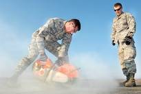 Air Force Col. John Klein, left, commander of the 60th Air Mobility Wing, uses a concrete cutter while Air Force Staff Sgt. Jake Goettl observes during the Works With Airmen program at Travis Air Force Base, Calif., Aug. 19, 2016. Goettl is the airfield maintenance noncommissioned officer-in-charge with the 60th Air Mobility Wing. Air Force photo by Louis Briscese