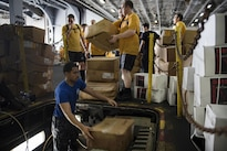 Sailors move cargo in the hangar bay of the aircraft carrier USS Dwight D. Eisenhower during a replenishment-at-sea with the fast combat support ship USNS Arctic in the Persian Gulf, Aug. 19, 2016. Navy photo by Seaman Apprentice Joshua Murray