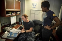 Navy Lt. Cynthia Parmley, left, reviews client intake forms with Navy Petty Office 1st Class Chardae Longshore in the legal office of the aircraft carrier USS Dwight D. Eisenhower in the Persian Gulf, Aug. 19, 2016. Navy photo by Seaman Apprentice Joshua Murray