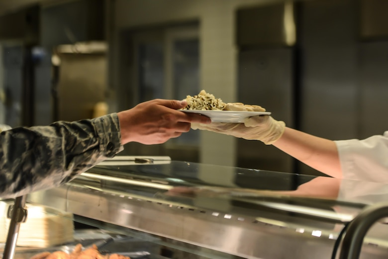 A food services Airman serves a customer at the Rheinland Inn Dining Facility, Aug. 29, 2016, Ramstein Air Base, Germany. The Rheinland Inn offers a wide variety of snacks, entrees, dessert and beverages. (U.S. Air Force photo/ Airman 1st Class Joshua Magbanua)