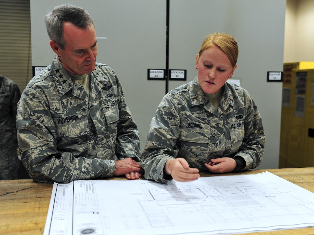 Lt. Gen. Darryl Roberson, commander of Air Education and Training Command, looks over proposed design changes to the 314th Aircraft Maintenance bay with 2nd Lt. Carissa Dobbins, 314th AMXS Sortie Support Flight commander, Aug. 22, 2016, at Little Rock Air Force Base, Ark. Dobbins explained that the expansion would improve storage for equipment and tools as well as provide more room for the maintenance teams to prepare for the day.  (U.S. Air Force photo by Staff Sgt. Jeremy McGuffin)