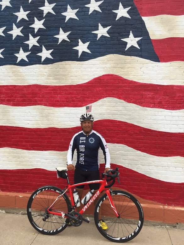 Chief Master Sgt. Julio Flores, 544th Intelligence, Surveillance and Reconnaissance Group superintendent, Peterson Air Force Base, Colo., poses in front of a United States flag mural in Sigourney, Iowa on July 28. Flores joined 140 other Airmen in completing the 2016 [Des Moines] Register's Annual Great Bike Ride Across Iowa, simply known as RAGBRAI. (courtesy photo)