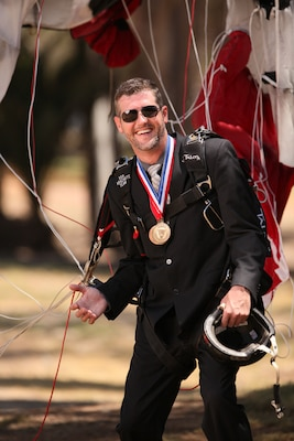 NSWC Corona engineer Taylor Cole poses wearing his parachute rig and championship medals.