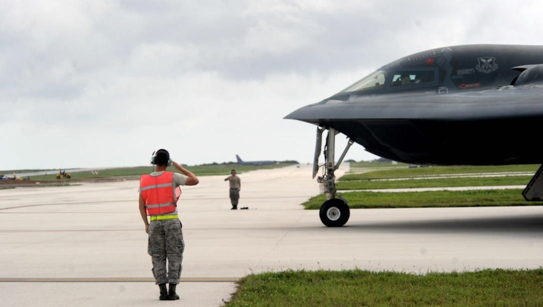 U.S. Air Force Staff Sgt. Matthew Helms, left, and Staff Sgt. Joshua Layton, both dedicated crew chiefs assigned to the 509th Aircraft Maintenance Squadron, salute pilots of a B-2 Spirit aircraft as they begin to taxi onto the runway Aug. 22, 2016 at Andersen Air Force Base, Guam. Thanks to its subsonic speeds and it's nearly 7,000 mile un-refueled range, the B-2 Spirit is capable of bringing massive firepower, in a short time, anywhere on the globe through the most challenging defenses. (U.S. Air Force photo by Senior Airman Jovan Banks)