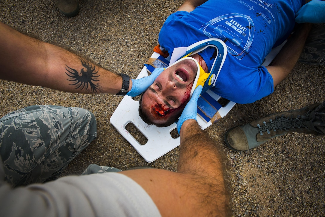 Emergency Medical Technicians from Offutt Air Force Base, Neb., treat a car accident trauma patient during the 2016 EMT Rodeo Aug. 25, 2016, at Cannon Air Force Base, N.M. Cannon's EMT Rodeo tests the skills of medical professionals from across the Air Force through a series of innovative high-pressure scenarios. (U.S. Air Force photo by Staff Sgt. Eboni Reams/Released)