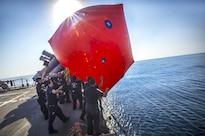 "Sailors throw a ""killer tomato,"" or inflatable target, into the water during a live-fire exercise aboard the guided-missile cruiser USS Monterey in the Arabian Gulf, Aug. 26, 2016. The Monterey is supporting maritime security operations and theater security cooperation efforts in the U.S. 5th Fleet area of operations. Navy photo by Petty Officer 2nd Class William Jenkins"