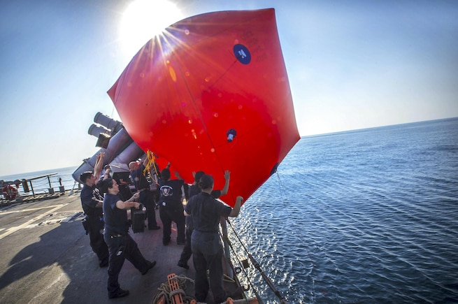 "Sailors throw a ""killer tomato,"" or inflatable target, into the water during a live-fire exercise aboard the USS Monterey in the Arabian Gulf, Aug. 26, 2016. The Monterey is supporting maritime security operations and theater security cooperation efforts. Navy photo by Petty Officer 2nd Class William Jenkins"