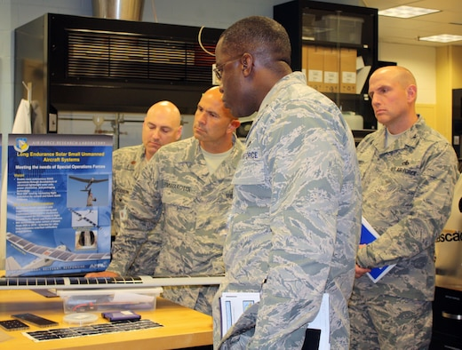 WRIGHT-PATTERSON AIR FORCE BASE, Ohio – Brig. Gen. Stacey T. Hawkins, Director, Logistcs, Engineering and Force Protection, Air Mobility Command (center) learns more about additive manufacturing capabilities for functional materials during a visit to the Materials and Manufacturing Directorate, Air Force Research Laboratory, Aug. 26. The laboratory visit was part of a larger tour of AFRL facilities to gain in-depth knowledge of current capabilities for additive manufacturing technology. The visit included a directorate overview, discussions on additive manufacturing applications and visits to multiple research laboratories, highlighting 3-D printing capabilities for metals, polymer-based materials and functional material applications. AMC is exploring the possibilities of using additive manufacturing for replacement parts for aircraft during the life-cycle maintenance process. (Air Force photo by Marisa Novobilski/released)