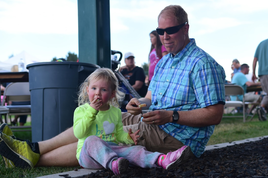 Capt. David Edsen, Aerospace Data Facility Colorado commander's executive officer, sits with his daughter Lily at FunFest Aug. 26, 2016, on Buckley Air Force Base, Colo. FunFest provided members of the Buckley community with a variety of different attractions for all ages to enjoy. (U.S. Air Force photo by Senior Airman Luke W. Nowakowski/Released)