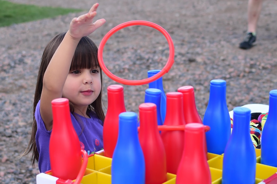 Kaylee, a Buckley Air Force Base child, tosses a ring while playing a game during FunFest Aug. 26, 2016, on Buckley AFB, Colo. Dozens of games and attractions were set up in order to entertain the Buckley community in attendance during FunFest. (U.S. Air Force photo by Senior Airman Luke W. Nowakowski/Released)