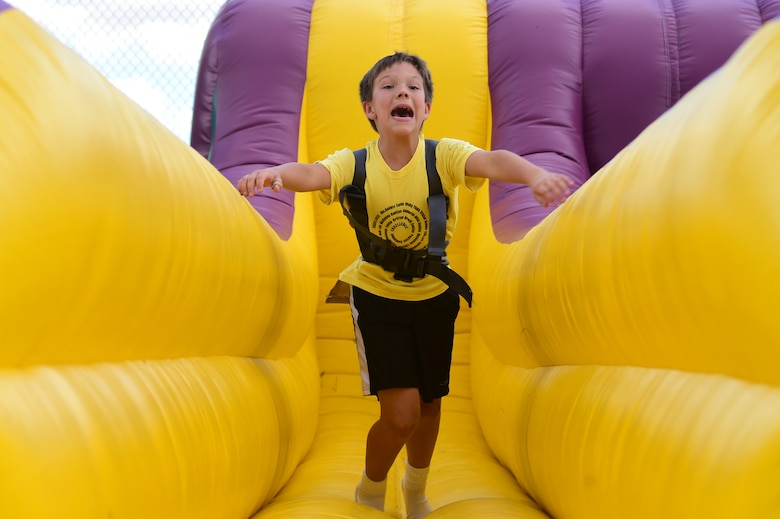 Sam, a Buckley Air Force Base child, runs as hard as he can while harnessed to bungee cord during FunFest Aug. 26, 2016, on Buckley AFB, Colo. A variety of inflatable games were erected as attractions for children of the base community to play on. (U.S. Air Force photo by Senior Airman Luke W. Nowakowski/Released)