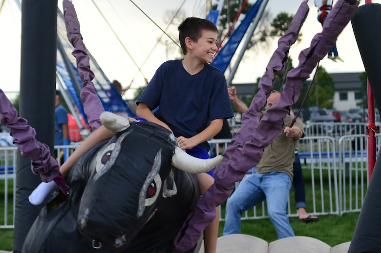 Tristan, a Buckley Air Force Base child, holds on tight while riding an inflatable bull during FunFest Aug. 26, 2016, on Buckley AFB, Colo. FunFest provided members of the Buckley community with a variety of different attractions for all ages to enjoy. (U.S. Air Force photo by Senior Airman Luke W. Nowakowski/Released)