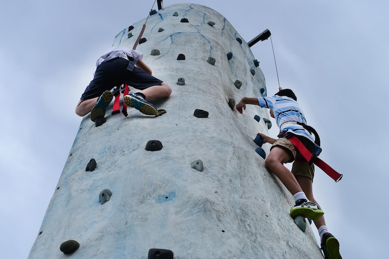 Buckley Air Force Base children, climb a rock wall during FunFest Aug. 26, 2016, on Buckley AFB, Colo. Dozens of games and attractions were set up in order to entertain the Buckley community in attendance during FunFest. (U.S. Air Force photo by Senior Airman Luke W. Nowakowski/Released)
