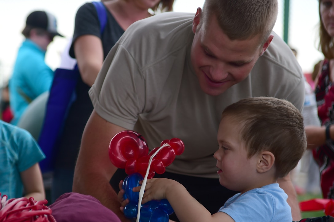 U.S. Army Sgt. Gary Andrews, 743rd Military Intelligence Battalion analyst, watches as his son James receives a balloon that has been sculpted to look like spiderman at FunFest Aug. 26, 2016, on Buckley Air Force Base, Colo. FunFest provides attraction for all ages and is an annual fair for the base community. (U.S. Air Force photo by Senior Airman Luke W. Nowakowski/Released)