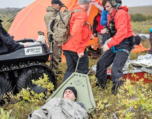 Pararescuemen from the 212th Rescue Squadron, Alaska Air National Guard, move a simulated casualty to their Arctic Sustainment Package during exercise Arctic Chinook, near Kotzebue, Alaska, August 23. Arctic Chinook is a joint U.S. Coast Guard and U.S. Northern Command sponsored exercise which focuses on multinational search and rescue readiness to respond to a mass rescue operation requirement in the Arctic. (U.S. Air National Guard photo by Staff Sgt, Edward Eagerton/released)